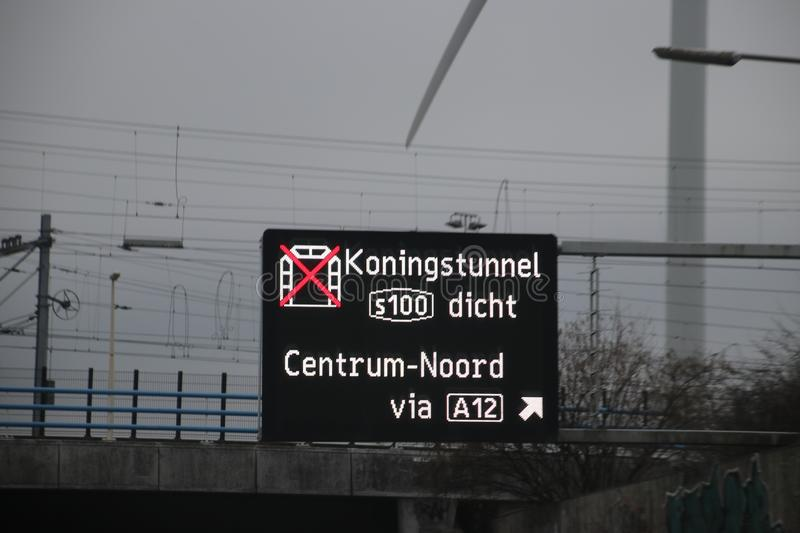 Dynamic route information panel warns for closed tunnel named Koningstunnel on S100 in The Hague on highway A4. royalty free stock photos
