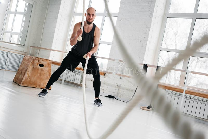 Dynamic shot of strong man workout with battle ropes at light gym stock image