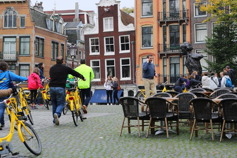 A dynamic street scene with yellow bikes royalty free stock photography