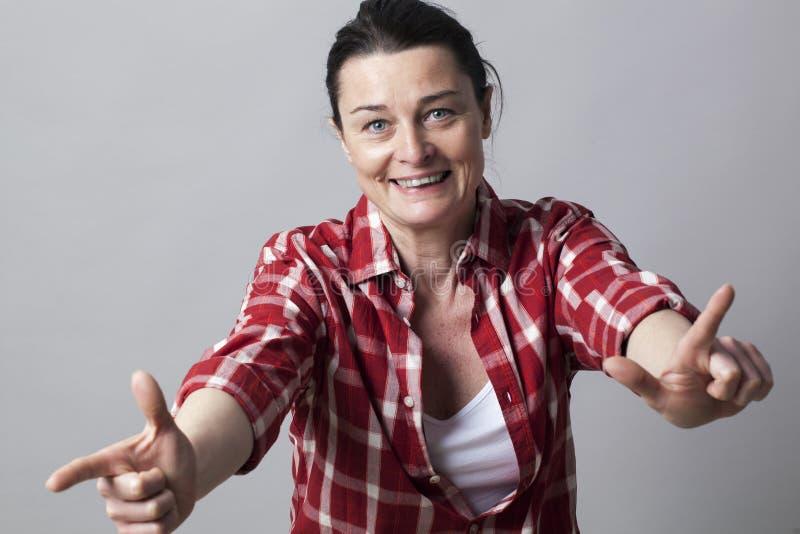 Dynamiczna piękna w średnim wieku kobieta używa ręki jak seksowni pistolety fotografia stock