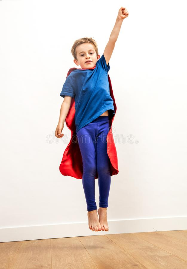 Dynamiczny dzieciaka dojechanie wysoki jak potężny bohater, lata obraz stock