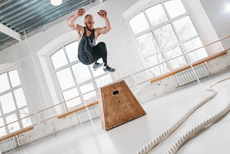 Dynamiczny strzał sprawności fizycznej męska atleta skacze przy kwadratowym pudełkiem w crossfit gym obrazy royalty free