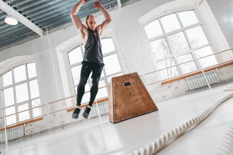 Dynamiczny strzał sprawności fizycznej męska atleta skacze przy kwadratowym pudełkiem w przecinającym gym zdjęcie stock