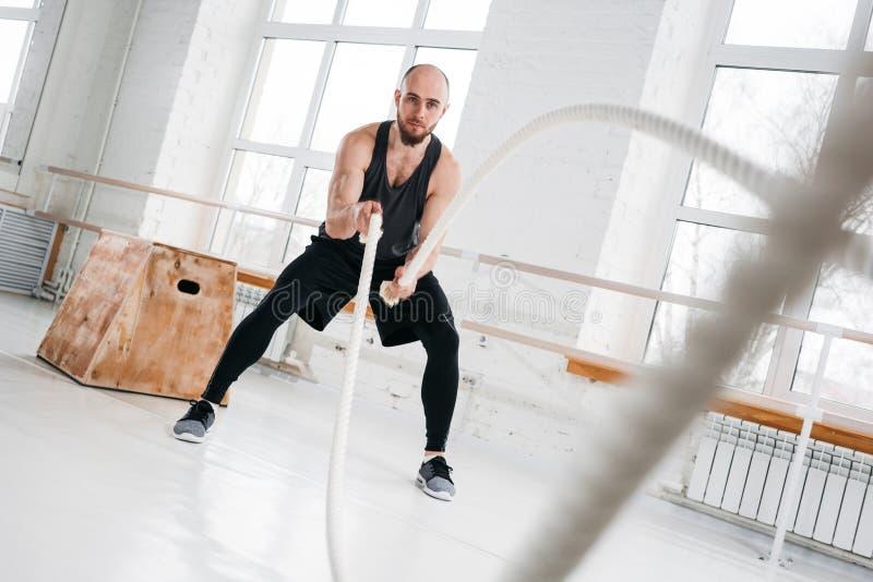 Dynamin strzał silnego mężczyzny trening z batalistycznymi arkanami przy lekkim gym fotografia royalty free