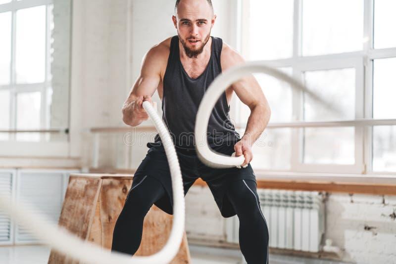 Dynamin strzał silnego mężczyzny trening z batalistycznymi arkanami przy lekkim gym obrazy royalty free