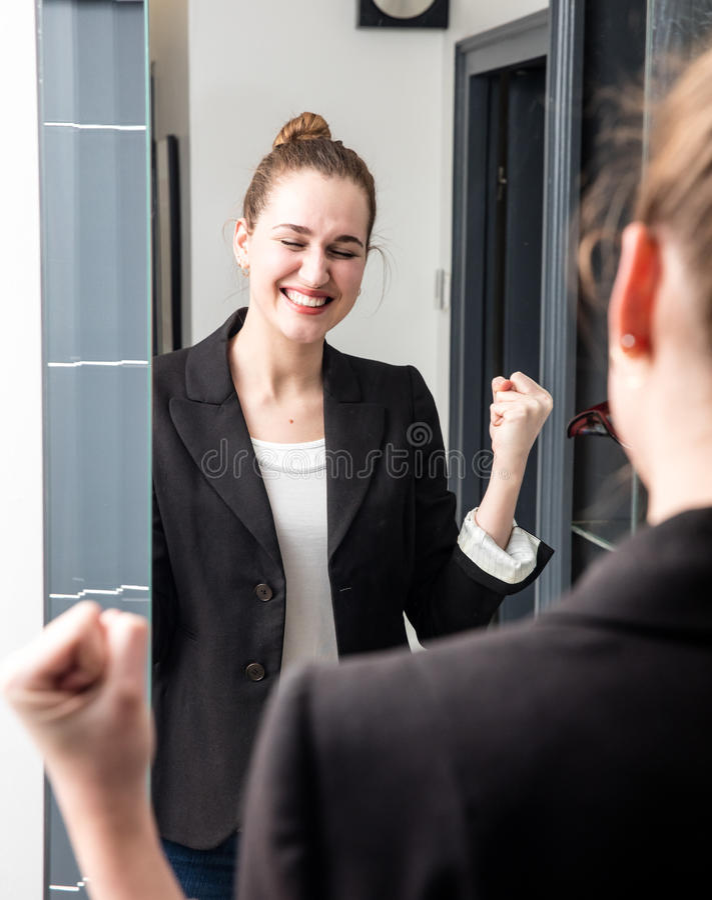 Dynamische jonge vrouw die met succesvolle die wapens glimlachen in spiegel worden opgeheven stock afbeeldingen