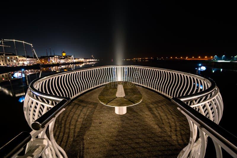 Dynamische mening van een verlichte architectuurbrug over een rivier tijdens de nacht stock foto's