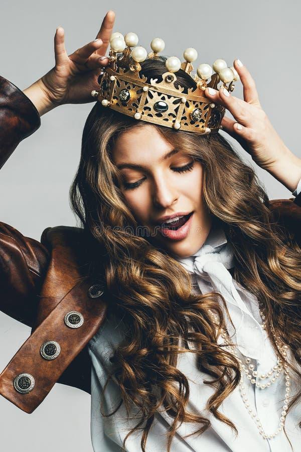 Dynamische vrouw in leerjasje met gouden kroon stock fotografie
