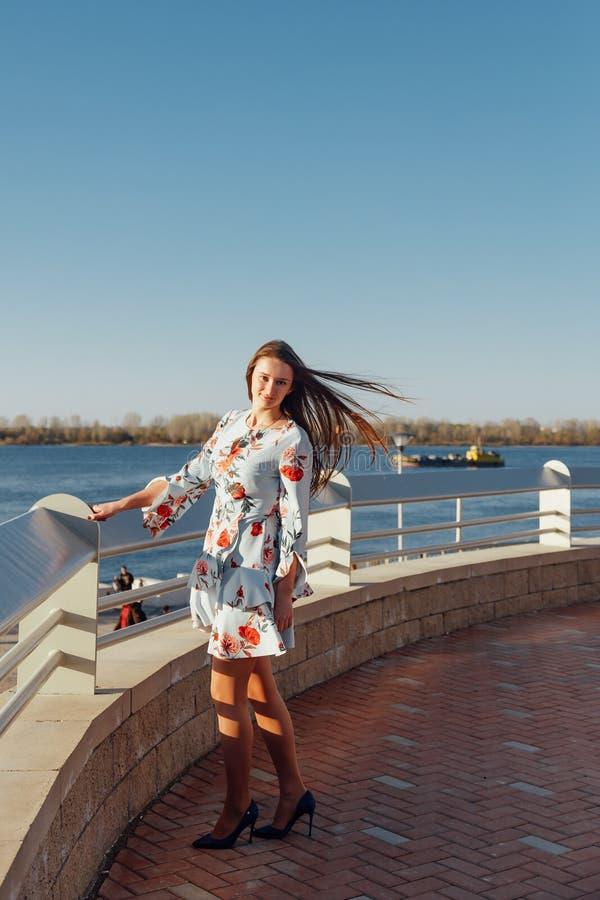 Dynamisches Modeart Portr?t eines jungen sch?nen M?dchens, das entlang die Ufergegend der Stadt geht stockfotografie