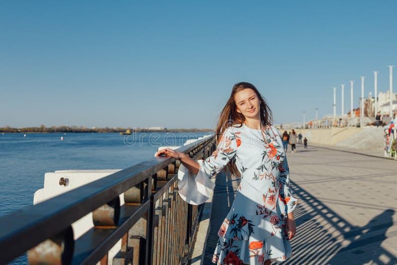 Dynamisk modestilstående av en ung härlig flicka som promenerar stranden av staden arkivbilder