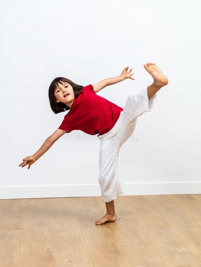 Dynamiskt barn som tycker om slåss tai-chi, kung fu eller Taekwondo arkivfoto