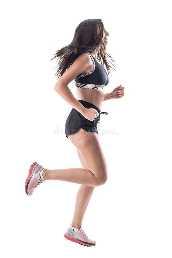 Dynamiskt foto från sidvyn av en ung kvinna med aktiv passning och långa hår royaltyfri fotografi