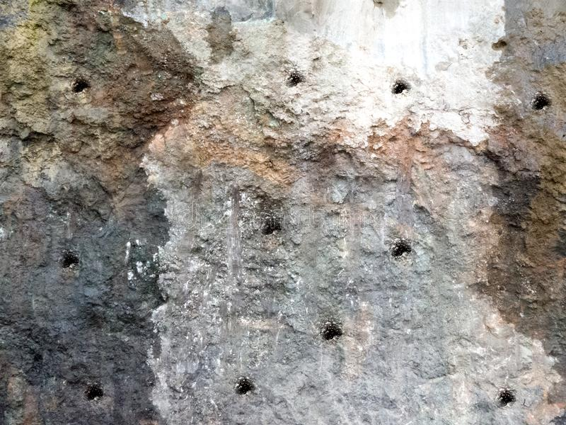 Dynamite Holes for explosive filing on a Mountain Rock. Holes for explosive filing on a Mountain Rock for the construction of roads stock photo
