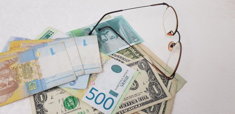 Dynars y dólares de Hryvnia cerca de las lentes en la tabla blanca fotografía de archivo libre de regalías