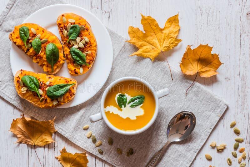 Dyniowa kremowa polewka Weganinu zdrowy jedzenie Śniadanie lub śniadanio-lunch na białym drewnianym tle fotografia royalty free