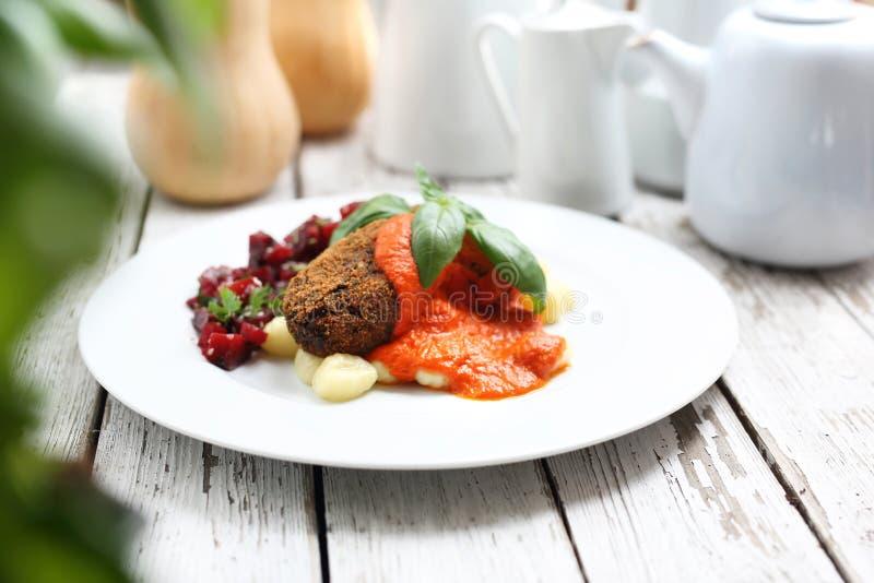 Dyniowi cutlets s?uzy? z pomidorowym kumberlandem na kluchach na gnocchi, piec ?wik?owa sa?atka zdjęcie stock