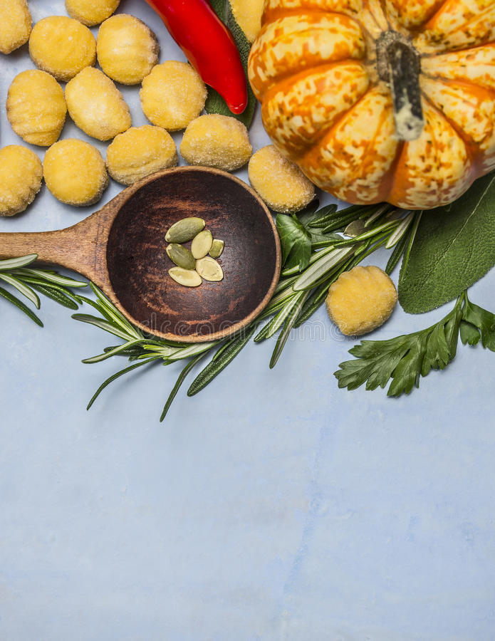 Dyniowy gnocchi z drewnianymi łyżkowymi migdału czerwonego pieprzu dyniowymi rozmarynami na błękitnym drewnianym tło odgórnego wi obraz stock