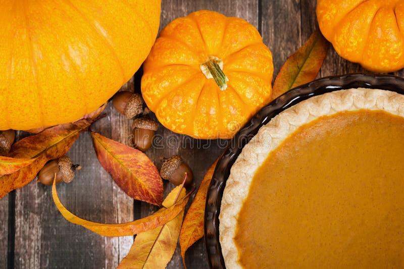 Dyniowy kulebiak z baniami i jesieni dekoracjami na wieśniaka stole zdjęcia royalty free
