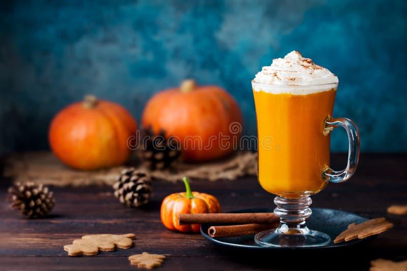 Dyniowy pikantności latte, smoothie z batożącą śmietanką Drewniany tło kosmos kopii obrazy stock