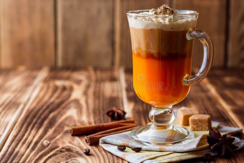 Dyniowy pikantności latte z batożącym cynamonem w szkle na nieociosanym drewnianym tle i śmietanką zdjęcia royalty free
