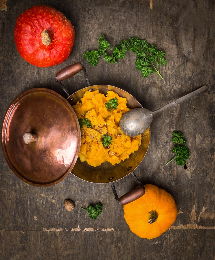 Dyniowy puree w rocznika garnku z czerwonymi i żółtymi dyniowymi owoc zdjęcia stock