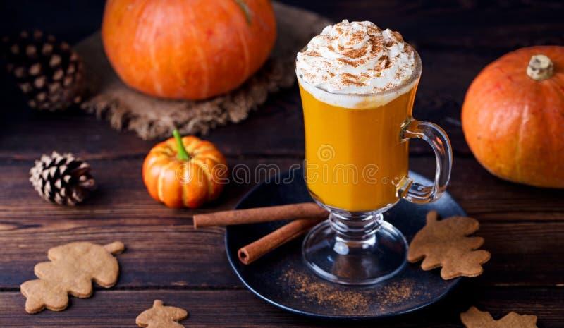 Dyniowy smoothie, pikantności latte Pijacki koktajl z batożącą śmietanką Drewniany tło zdjęcia royalty free