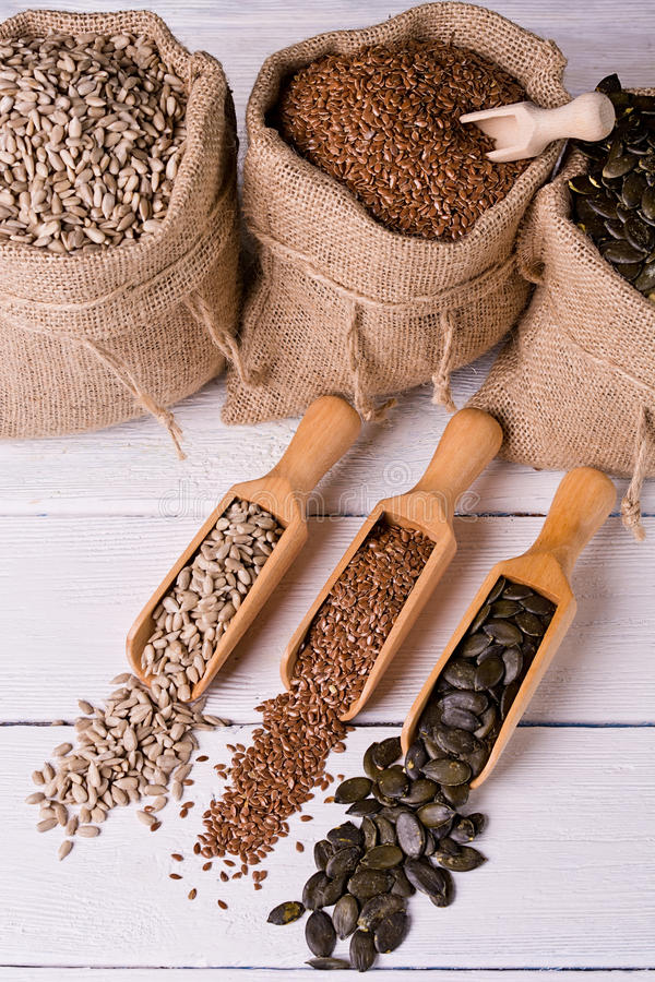 Dyniowych ziaren, słonecznika i lna ziarna w drewnianej łyżce, W tło jutowej torbie z ziarnami zdjęcia stock