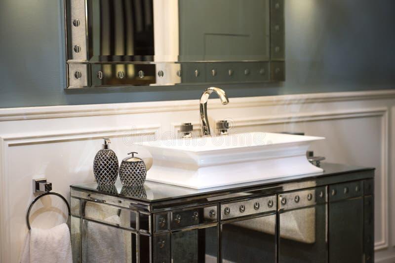 Dyr badrumvask och spegelförsett kabinett arkivfoto