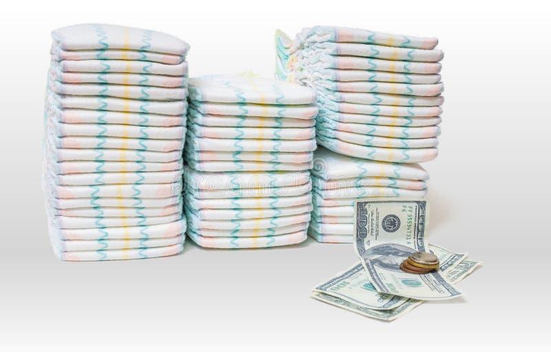 Dyr barnomsorg En hög av blöjor och pengar på vit bakgrund arkivfoton