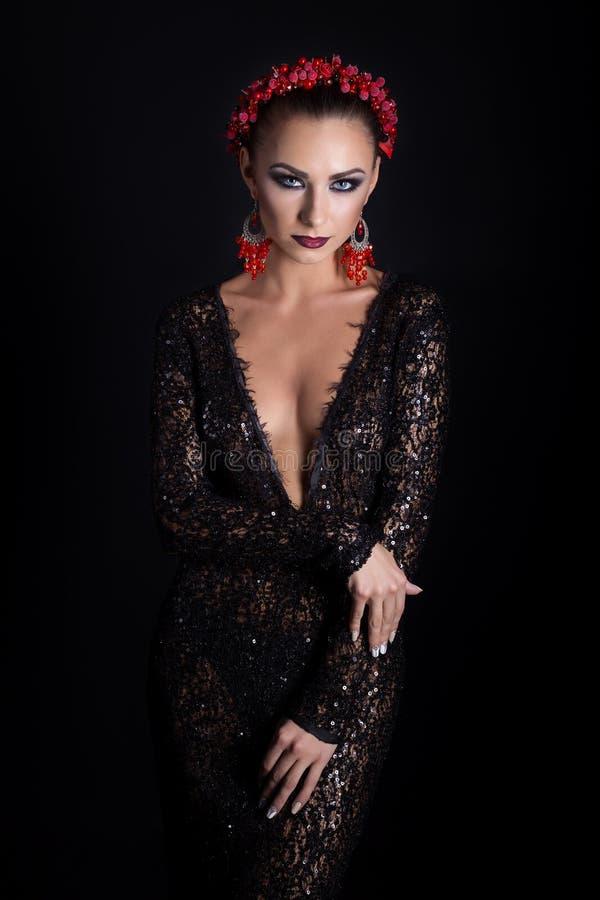 Dyr smyckenkransörhängen och cirkel på en härlig sexig elegant brunettflicka med ett ljust aftonsmink i en svart även royaltyfria bilder