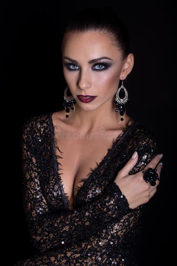 Dyr smyckenkransörhängen och cirkel på en härlig sexig elegant brunettflicka med ett ljust aftonsmink i en svart även arkivbild