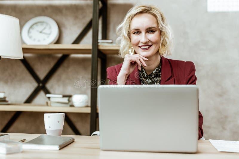 Dyrbar härlig blond kvinna som trycker på hennes haka med en hand arkivbilder
