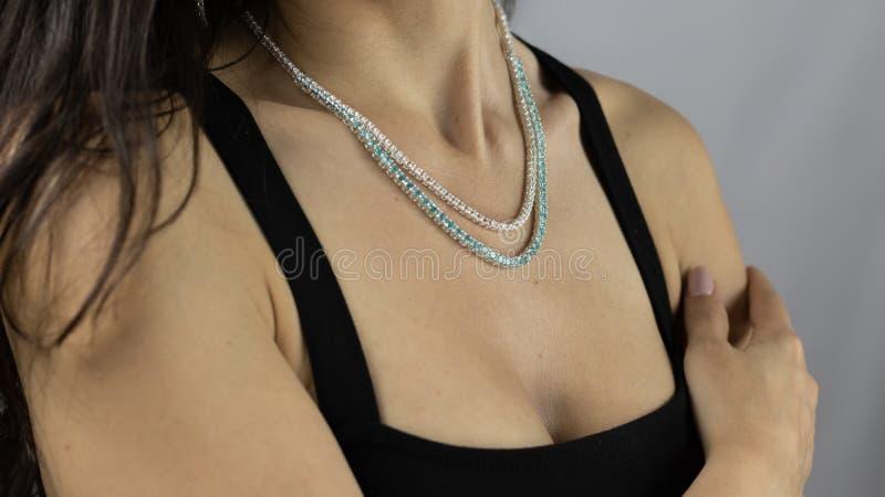 Dyrbar halsband med ljusa gemstones p? halsen av en ung kvinna royaltyfri bild