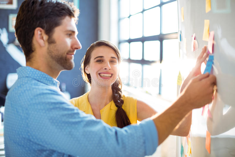 Dyrektor wykonawczy i współpracownik stawia kleiste notatki na whiteboard obraz royalty free