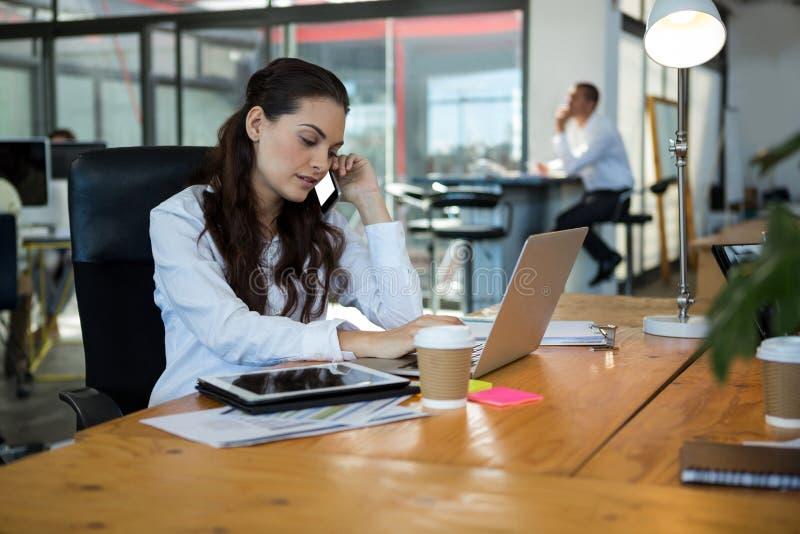 Dyrektor wykonawczy opowiada na telefonie komórkowym podczas gdy używać laptop przy biurkiem fotografia royalty free