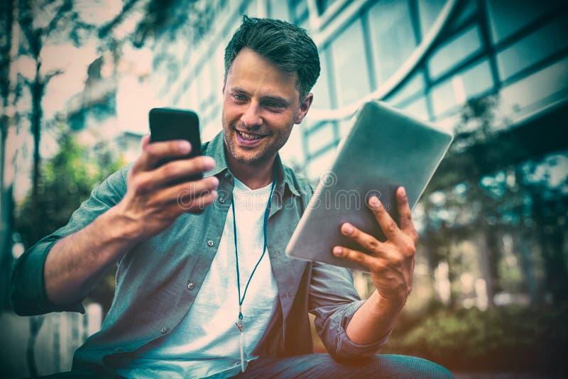 Dyrektor wykonawczy używa telefon komórkowego i cyfrową pastylkę przeciw budynkowi biurowemu zdjęcia stock