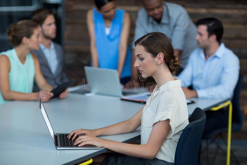 Dyrektora wykonawczego obsiadanie na stołowym i używa laptopie zdjęcia stock