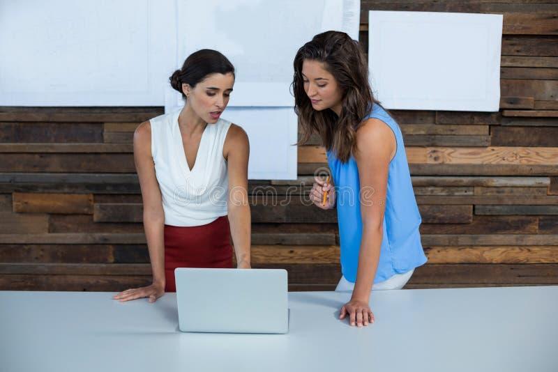 Dyrektory wykonawczy dyskutuje nad laptopem obraz stock
