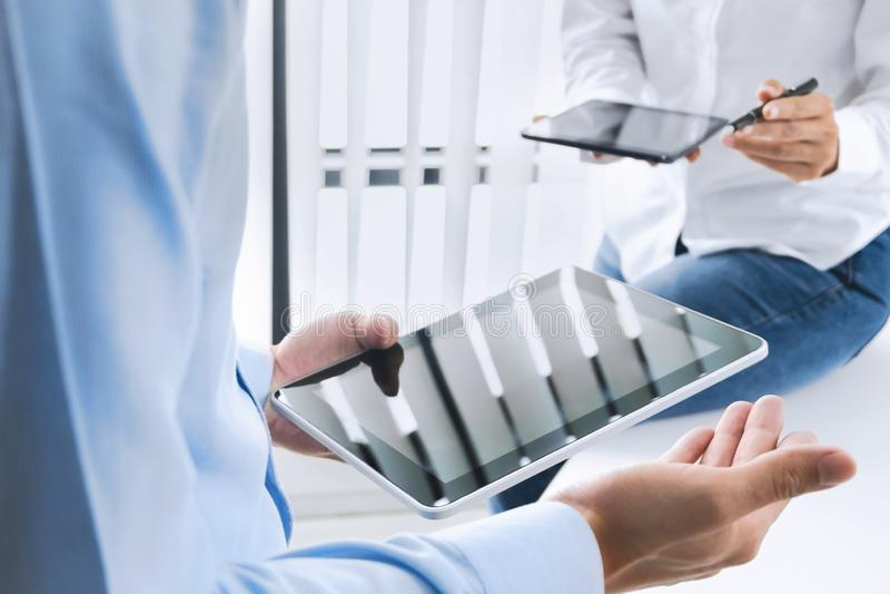 Dyrektory wykonawczy pracuje wpólnie i używa cyfrową pastylkę przy miejsce pracy obrazy royalty free