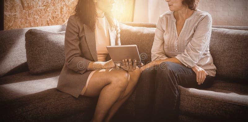 Dyrektory wykonawczy siedzi na kanapie i dyskutuje nad cyfrową pastylką zdjęcie royalty free