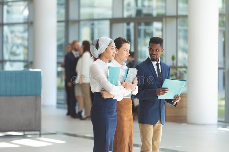 Dyrektory wykonawczy stoi z kartotekami w kuluarowym biurze obraz royalty free