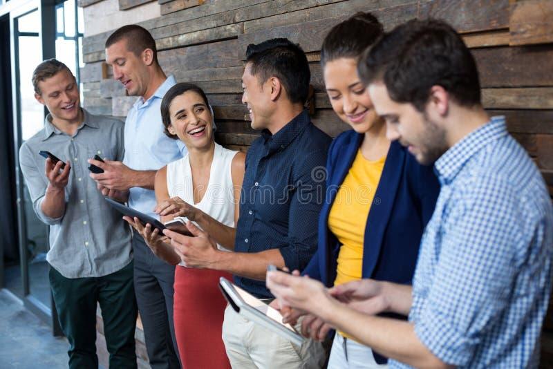 Dyrektory wykonawczy używa telefon komórkowego i cyfrową pastylkę obrazy royalty free