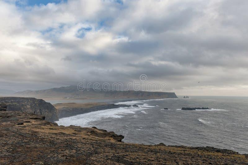 Dyrholaey Area in Iceland. Close to Black Sand Beach. Sunrise. Cloudy Sky. Wide Angle. stock photo