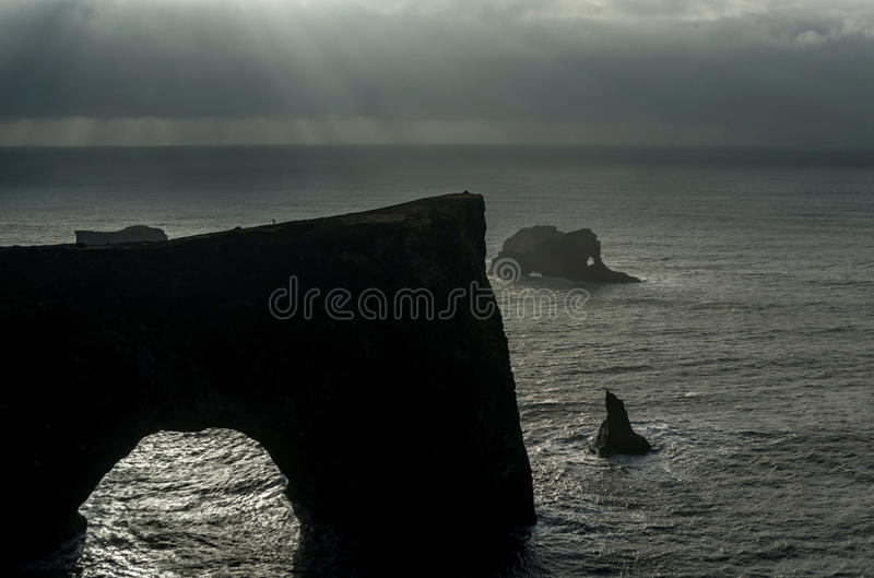 Dyrholaey Area in Iceland. Close to Black Sand Beach. Sunrise. Rocks in Background. Cloudy Sky. royalty free stock photo