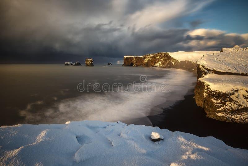 Dyrholaey cape over black sand beach stock photography