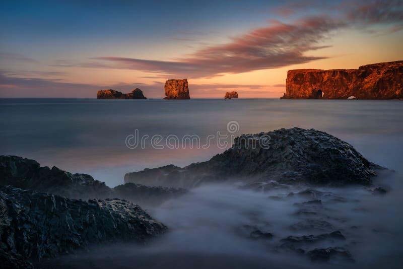 Dyrholaey coastline. Rocks of Dyrholaey black beach in sunrise light, Iceland stock images