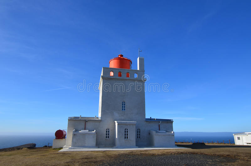 Dyrholaey Lighthouse Has a White Tower and Red Lantern. Iceland`s Dyrholaey Lighthouse on the sea cliffs of Vik royalty free stock photos