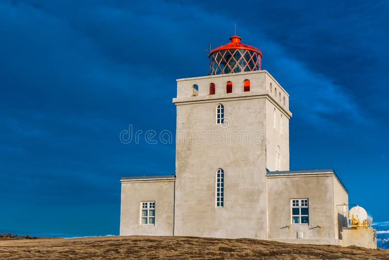 The Dyrholaey lighthouse in Iceland stands guard in stormy skies. The Dyrholaey lighthouse in Iceland towers over the landscape and stands guard in stormy skies stock photography