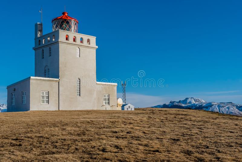 The Dyrholaey Lighthouse towers over the landscape in Iceland. The Dyrholaey Lighthouse towers over the landscape around it in Iceland stock photo