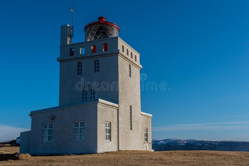 The Dyrholaey Lighthouse towers over the landscape in Iceland. The Dyrholaey Lighthouse towers over the landscape around it in Iceland royalty free stock images